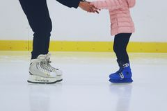 Father teaching daughter to skate at ice-skating rink stock photos