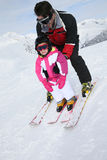 Father teaching her daughter how to ski Royalty Free Stock Photo