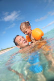 Father teaching her daughter how to swim in the sea Royalty Free Stock Photography