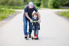 Father teaching his adorable toddler daughter to ride kick scoot Stock Image