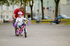 A father teaching his daughter to ride a bicycle Royalty Free Stock Image