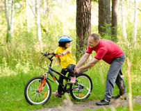 Father teaching his daughter to ride a bike Royalty Free Stock Photos