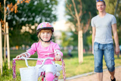 Father teaching his daughter to ride a bike Royalty Free Stock Images