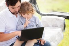 Father teaching his daughter using laptop computer. Royalty Free Stock Images
