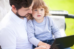 Father teaching his daughter using laptop computer Stock Image