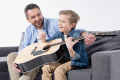 Father teaching his excited son to sing and play on guitar Royalty Free Stock Photo