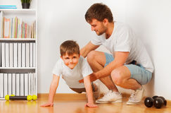 Father teaching his kid son pushing ups at home Stock Photo