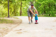 Father teaching his little daughter to ride kid scooter at the park on a sunny summer day royalty free stock images
