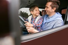 Father teaching his little son to drive   car. Father teaching his little son to drive a car Royalty Free Stock Photos
