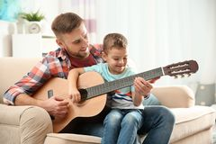 Father teaching his little son to play guitar stock images