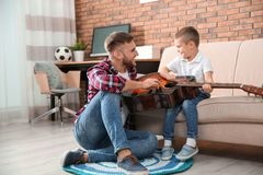 Father teaching his little son to play guitar royalty free stock images