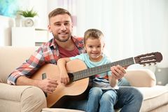Father teaching his little son to play guitar stock photo