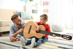 Father teaching his little son to play guitar royalty free stock photo
