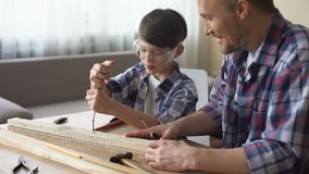Father teaching his smiling son carpentry, little boy using screwer at workshop. Stock footage stock video footage