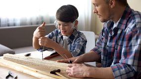 Father teaching his smiling son carpentry, little boy using screwer at workshop royalty free stock image