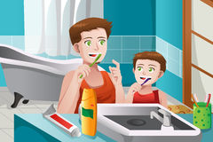 Father teaching his son how to brush his teeth Stock Photos