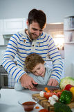 Father teaching his son how to chop vegetables. In the kitchen at home royalty free stock image