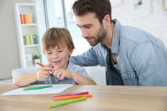 Father teaching his son how to draw. Daddy with little boy making drawings at home royalty free stock image