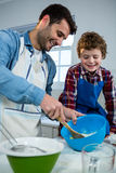 Father teaching his son how to make cup cake. Father teaching his son how to make cupcake in the kitchen stock image