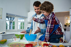 Father teaching his son how to make cupcake. In the kitchen stock photo