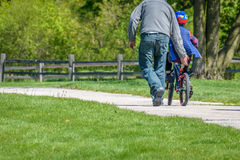 Father teaching his son how to ride a bike. Low angle of a man and child learning to ride a bicycle outside at park Stock Image