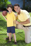 Father Teaching His Son To Play American Football. A father teaching his son how to play American football outside in sunshine Royalty Free Stock Images