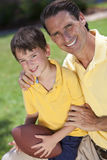 Father Teaching His Son To Play American Football. A father teaching his son how to play American football outside in sunshine royalty free stock image