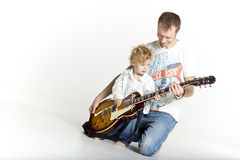 Father is teaching his son to play electric guitar Stock Photography
