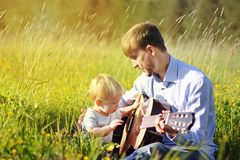 Father teaching his son to play guitar on summer field. Time together dad and son.  stock images
