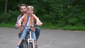 Father teaching his son to ride bicycle. father and son family concept. stock video