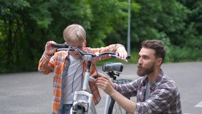 Father teaching his son to ride bicycle. father and son family concept. stock footage