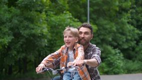 Father teaching his son to ride bicycle. father and son family concept. stock video footage