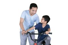 Father teaching his son to ride a bicycle on studio royalty free stock photo
