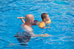 Father teaching his son to swim in outdoor swimming pool Royalty Free Stock Image