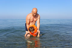 Father teaching his son to swim in sea Royalty Free Stock Photography