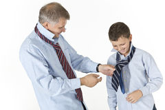 Father is teaching his son to tie a knot on a tie. Isolated on white son and father Stock Photo