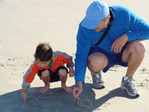 Father teaching his son to write. A letters on the sand stock images