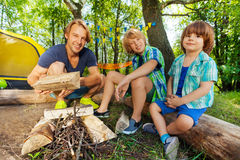 Father teaching his two sons make a camp fire Royalty Free Stock Image