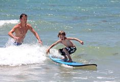 Father teaching his young son how to surf stock photography