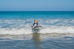 Father teaching his young son how to surf in the sea on vacation or holiday. Travel and sports with children concept.  royalty free stock photos