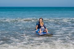 Father teaching his young son how to surf in the sea on vacation or holiday. Travel and sports with children concept.  royalty free stock photography