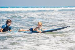 Father teaching his young son how to surf in the sea on vacation or holiday. Travel and sports with children concept.  stock photography