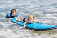 Father teaching his young son how to surf in the sea on vacation or holiday. Travel and sports with children concept.  stock photos