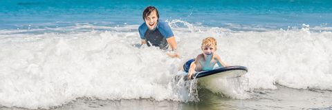 Father teaching his young son how to surf in the sea on vacation or holiday. Travel and sports with children concept. BANNER, long format stock photos