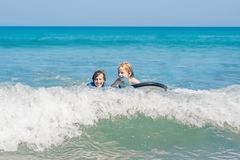 Father teaching his young son how to surf in the sea on vacation or holiday. Travel and sports with children concept.  royalty free stock image