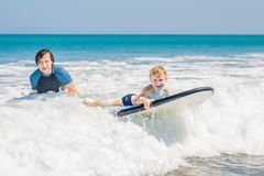 Father teaching his young son how to surf in the sea on vacation or holiday. Travel and sports with children concept.  stock images