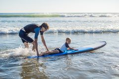 Father teaching his young son how to surf in the sea on vacation or holiday. Travel and sports with children concept.  stock image