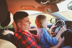 Father teaching kid daughter to drive a car, family traveling stock images