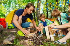 Father teaching kids to make a camp fire in forest. Portrait of young father teaching his kids making a camp fire in the forest royalty free stock photo