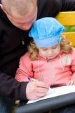 Father teaching little daughter to write Royalty Free Stock Photos
